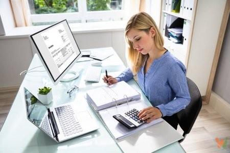 depositphotos_215584440-stock-photo-young-businesswoman-calculating-bill-computer